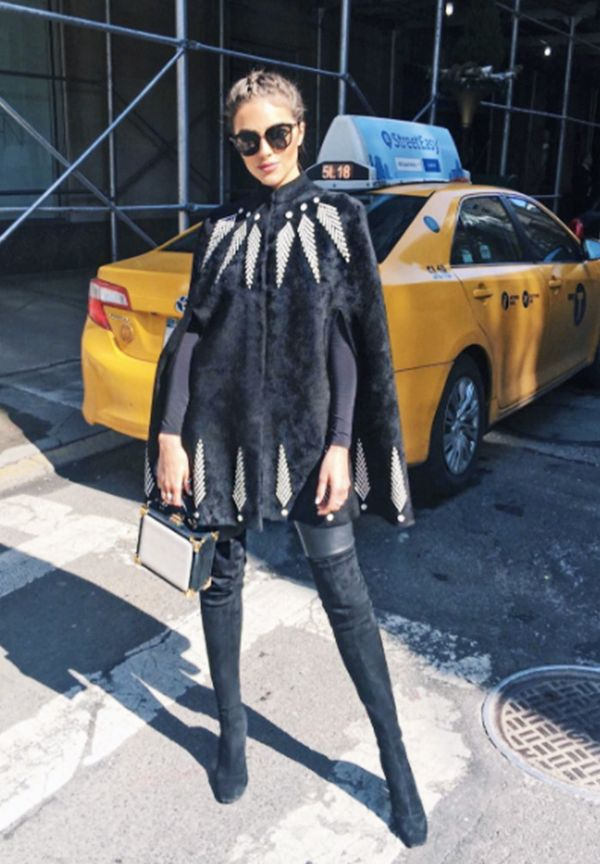 Olivia Culpo fashion style: Alexander McQueen cape, Nicholas Kirkwood Maeva Embellished Stretch-Suede Over-The-Knee Boots, Aspinal of London trunk clutch