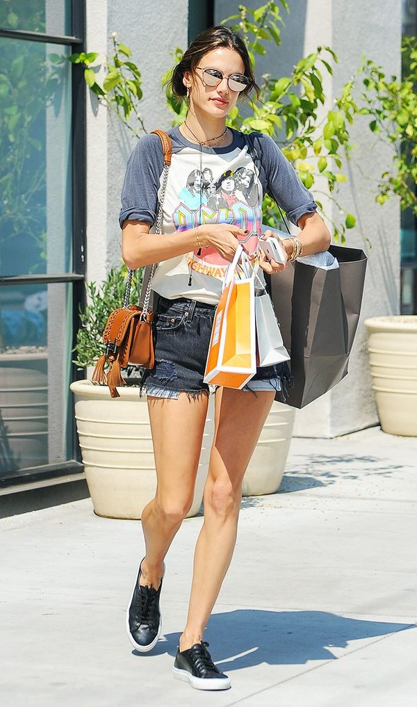 On Alessandra Ambrosio: Quay Tell Me Why Reflective Shades ($55); Junk Food Clothing Co. T-shirt; Tod's Double T Leather & Chain Shoulder Bag ($1765); Re/Done The Black High Rise...