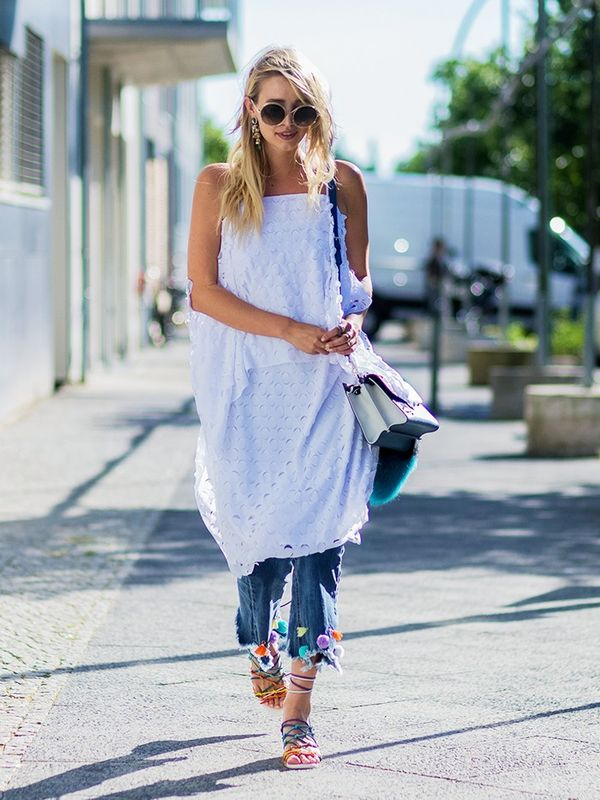 Style Notes: Who says you can't wear your favourite holiday clothes in the city? Layer a white dress over jeans and wear with bright sandals like Leonie Sophie Hanne now.