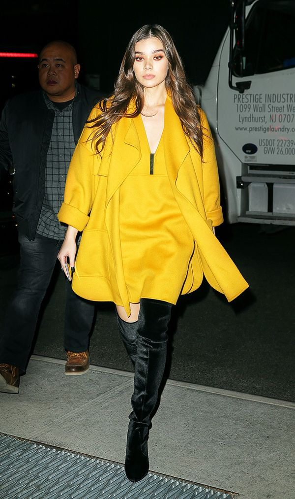 Hailee Steinfeld in yellow matching mini dress and jacket with thigh high velvet boots in New York City.