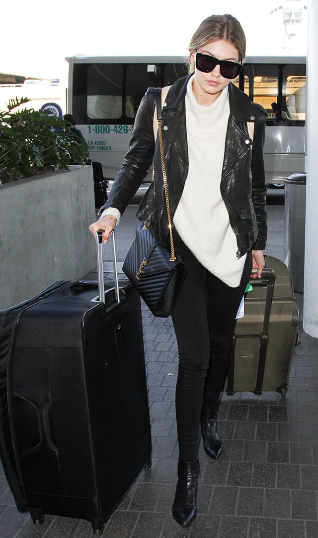 Gigi Hadid at LAX in white sweater, leather jacket, black pants, YSL bag