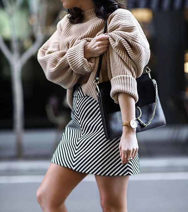 Beige sweater with oversized sleeves and diagonal striped black-and-white mini skirt