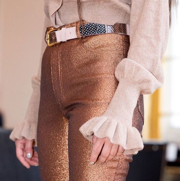 Shimmery blush sweater with tight wrists and flare ruffle sleeves, with golden pants and belt