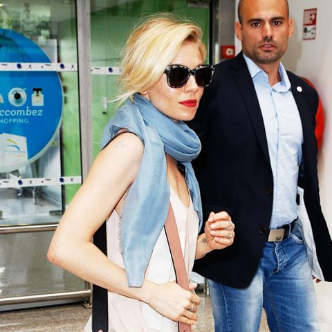 Sienna Miller wears skinny jeans and flat sandals.