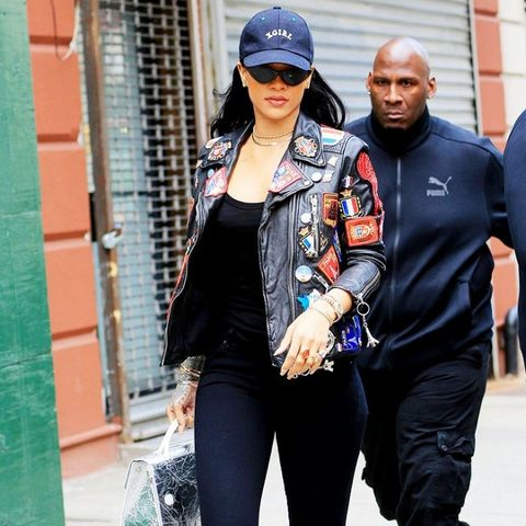 Rihanna wears skinny jeans and white ankle boots.