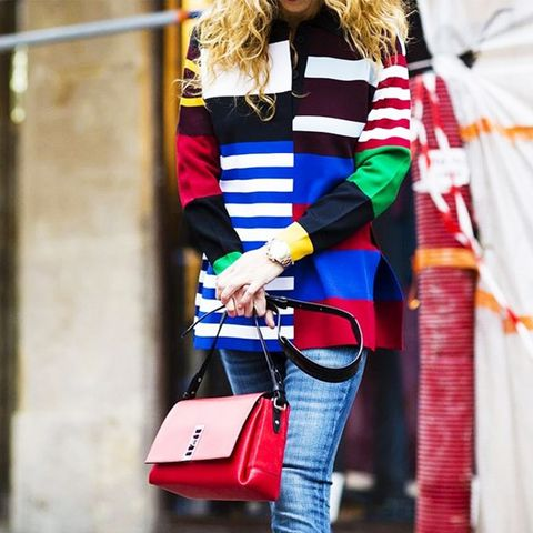 Colorful striped blouse, jeans, and red structured shoulder bag