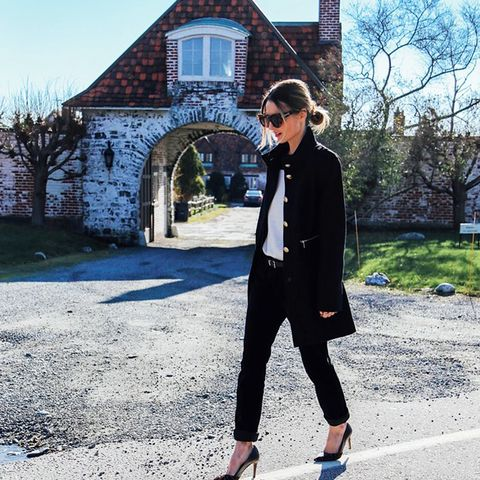 Black coat with gold buttons, white top, black pant, and black pointed heel