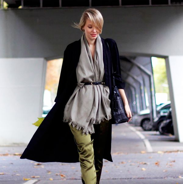 Black long line jacket with satin olive pants, scarf, and belt