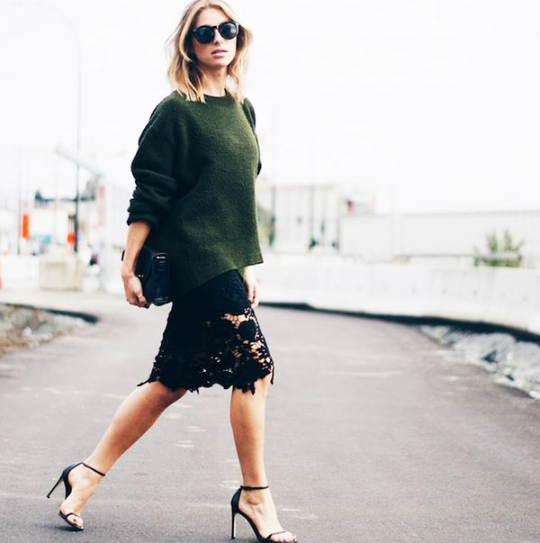 Oversized forest green sweater with lace detail skirt and black heeled sandals.