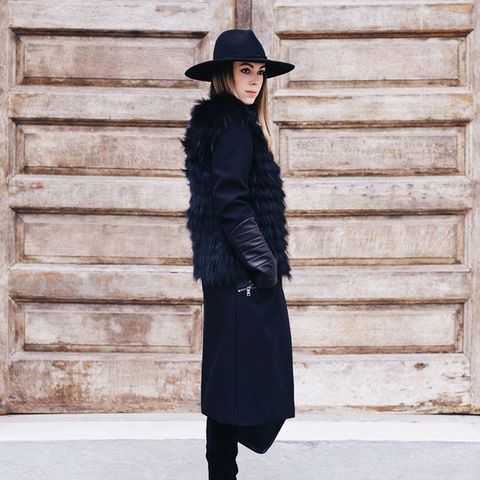 Black fur vest with black midi skirt, knee-high boots, and black felt hat