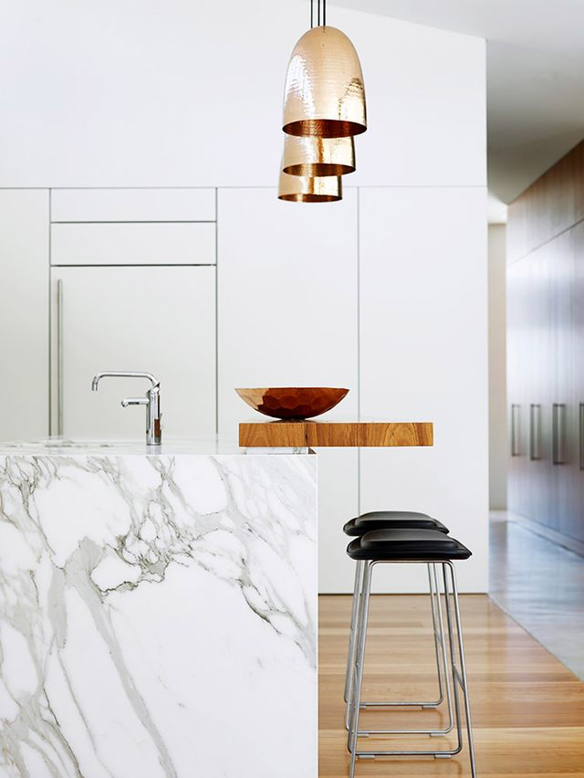 A Calacatta marble with a wide, abstract pattern makes for an unexpectedly fresh complement to organic wood and shiny copper pendants.