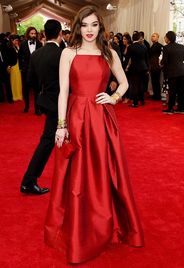 WHO: Hailee Steinfeld WEAR: Michael Kors crimson wool shantung pleated cross-back gown; Beladora jewelry; Edie Parker clutch.