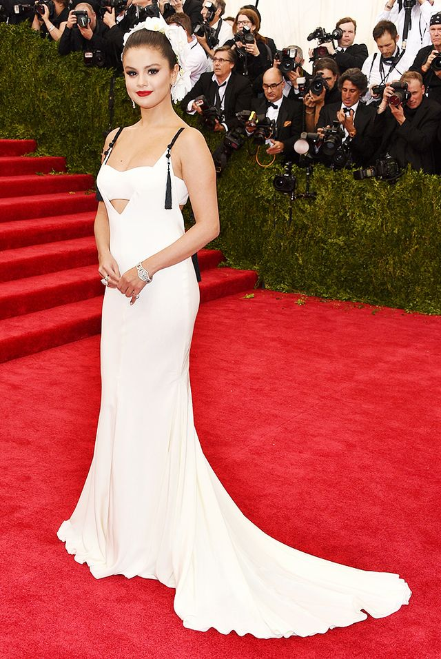 WHO: Selena Gomez WEAR: Vera Wang Collection custom ivory silk crepe V-neck bra top gown with plunging back and intricate black silk Chinese tassel accents.