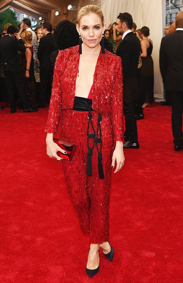 WHO: Sienna Miller WEAR: Thakoon red chiffon fringe sequined tuxedo with rope-tassel belt; Jacob & Co. custom earrings.
