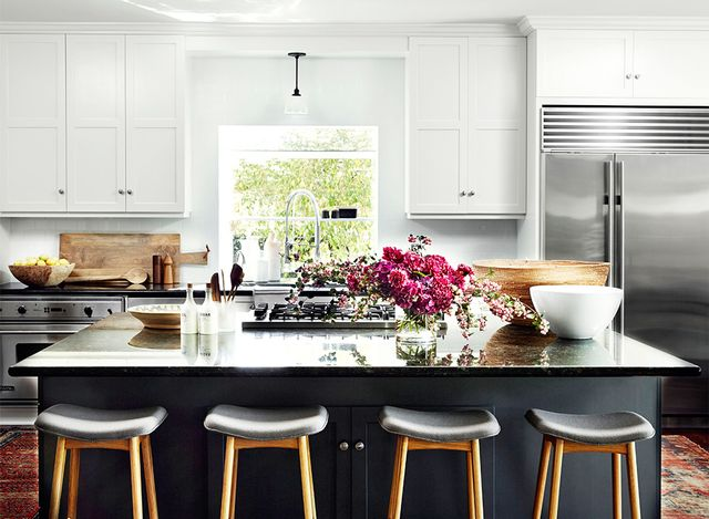 A warm black island pairs wonderfully with true white cabinetry in this kitchen space by Consort. Modern counter stools add interest while vintage floor rugs help the kitchen feel collected and...