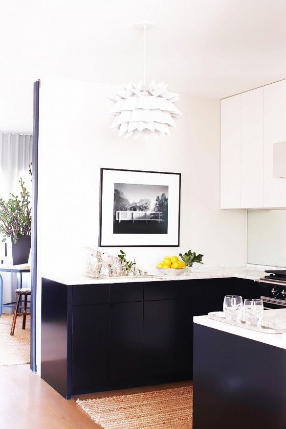 Black plain-front cabinets in a minimal San Francisco kitchen beautiful contrast with white marble counters and a mirrored backsplash, which visually doubles the space. A woven seagrass rug warms...