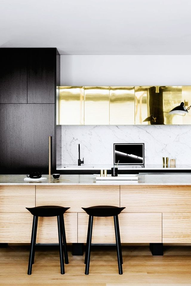 In this Australian home designed by Fiona Lynch, sleek black cabinets with hidden hardware mix with polished brass and marble surfaces to create a chic and modern installation.