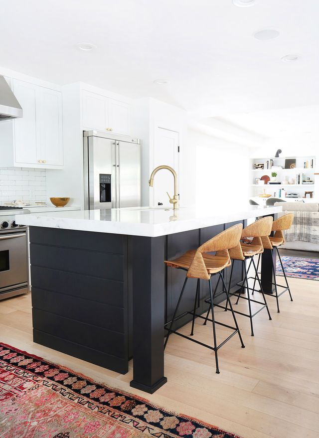 A deep black kitchen island adds contrast and definition to an airy and bright kitchen designed by Amber Interiors.