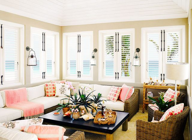 Woven furniture and a mix of patterns in a pleasing coral hue add texture and interest to this beach house. Subtle details like a striped lampshade on a bamboo floor lamp lend the space...