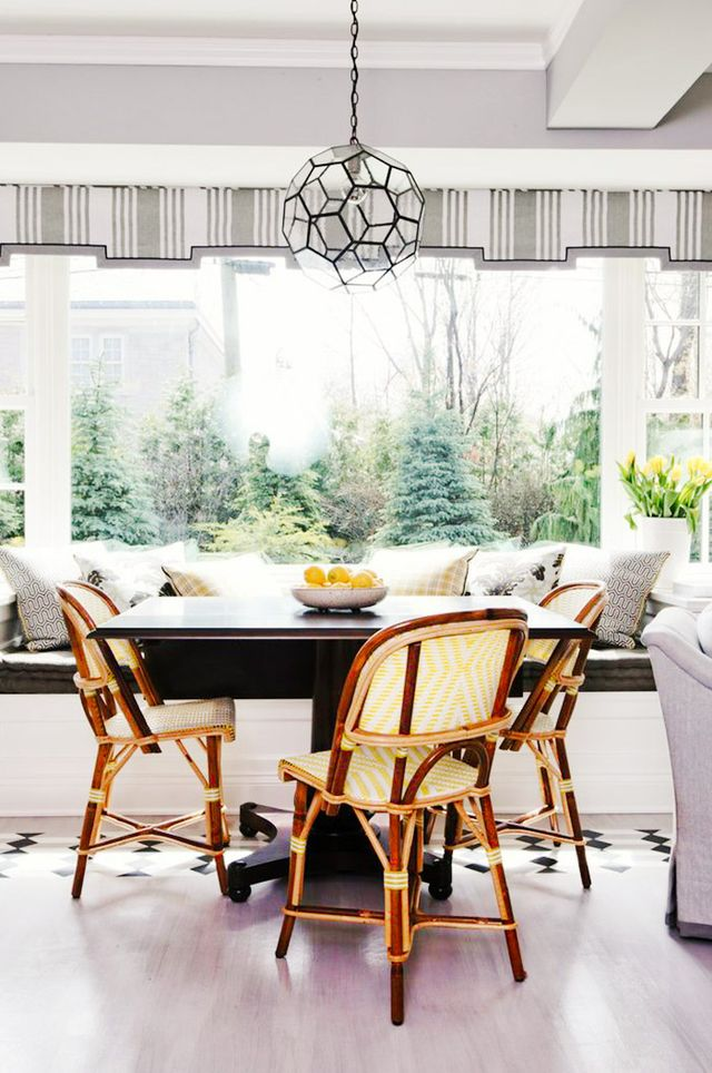 A charming striped valance over this room's expansive window offers a unique design element and feels like the awning of a particularly chic boutique. French bistro–style chairs add...