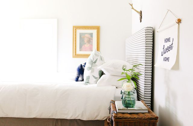 A subtle striped headboard and mix of patterned pillows give this room a cheery but soothing feeling. A woven trunk used as a nightstand injects textural interest into the space.
