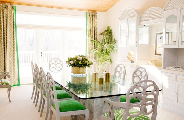 A set of classic Frances Elkins chairs upholstered in a saturated green color brings prep to this dining space. The drapery flaunts a subtle pattern with a contrast trim that coordinates with...