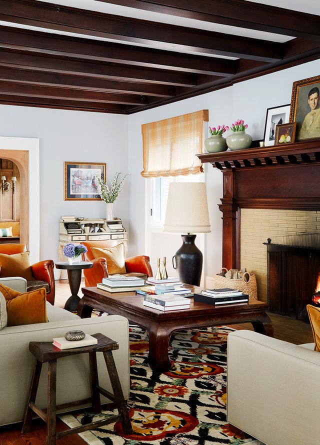 """In the living room, the fireplace mantel displays artwork from a variety of sources. """"There's everything from canvases painted by our daughter to a tablescape painted by my mom and a..."""