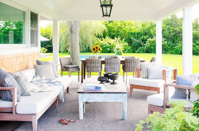 Neutral hues and comfortable throw pillows make this Hamptons porch space the perfect place to relax.