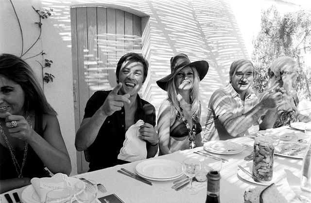 No shirt, no shoes, no problem. Brigitte Bardot and Alain Delon dine alfresco with friends while vacationing in St. Tropez.
