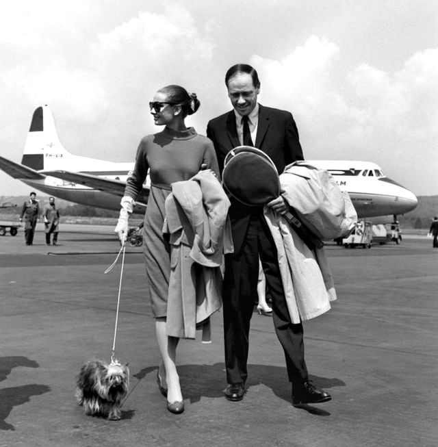 Audrey Hepburn gives meaning to jet-set style with her petite pooch at the Zürich Airport in Switzerland.