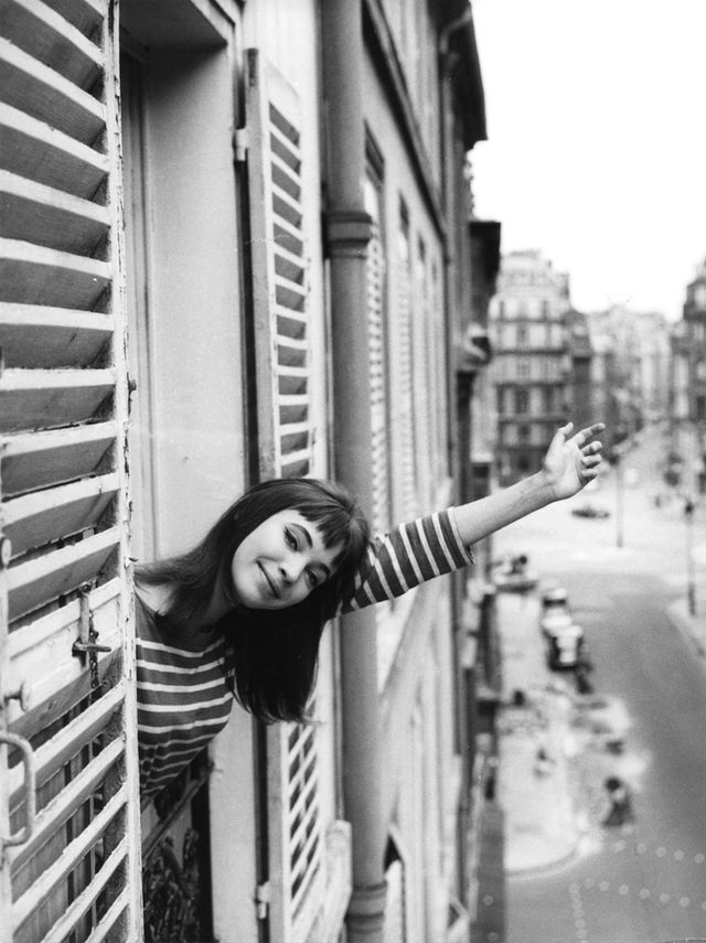 Darling of the French New Wave Anna Karina waves out the window of a Paris apartment building.