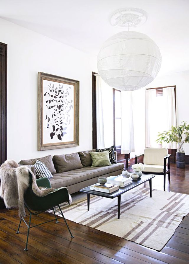 An airy, oversize paper globe pendant is the perfect topping to this neutral living room, and it highlights the room's enviably tall ceilings.