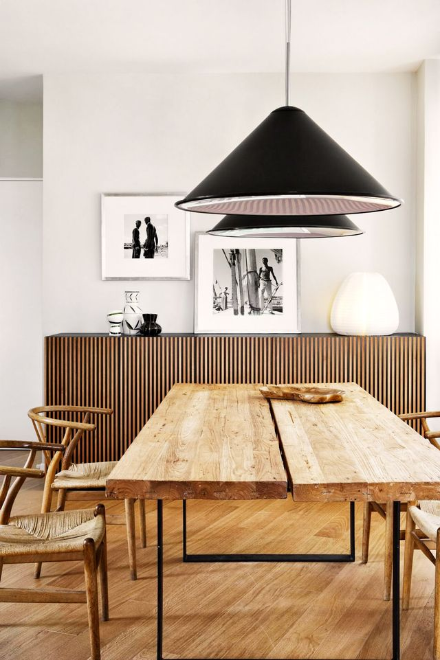 A sleek pair of cone-shaped black pendants serves as a modern counterpart to a dining space composed of rustic, monochromatic wood tones.