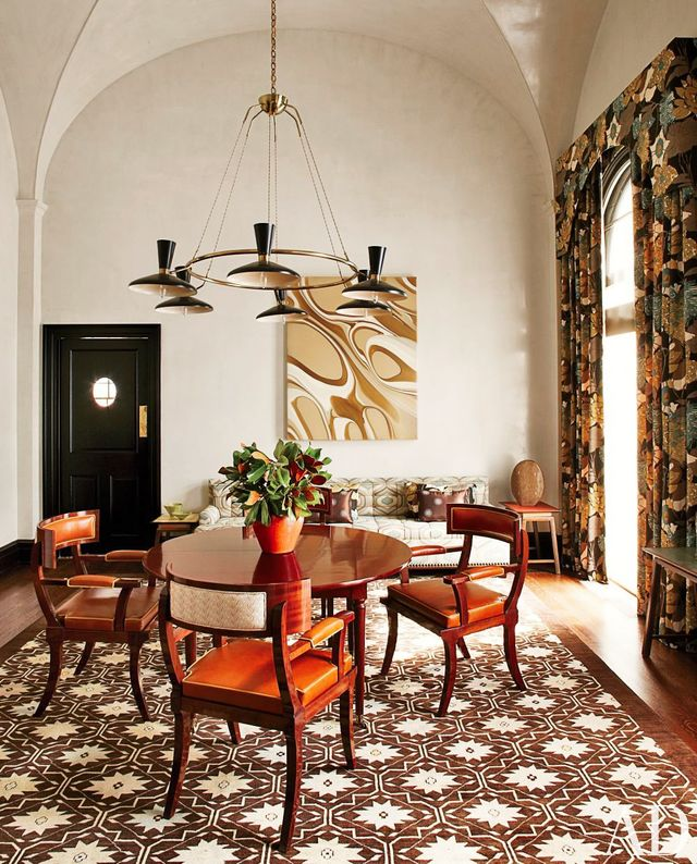A '50s Stilnovo chandelier floats above a rich mahogany-hued dining space.