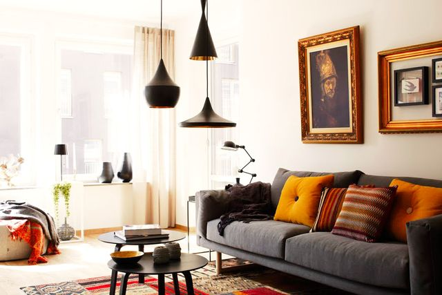 A trio of black pendants with unexpected bronze interiors adds modern pop to a masculine living room.