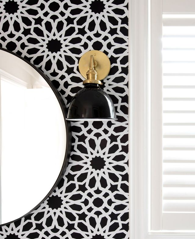 "One of the most statement-making elements is the F. Schumacher Agadir Screen Noir Wallpaper ($76/roll), which she hung on one wall. ""I knew I wanted to add one wall of bold wallpaper behind..."