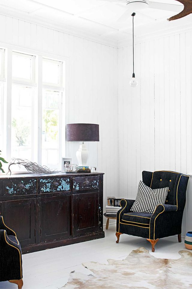 This room proves that white works with anything. Thevintage cabinet sits casually beside the Victorian-inspired armchairs, with an industrial pendant lamp hanging overhead and a cowhide rug...