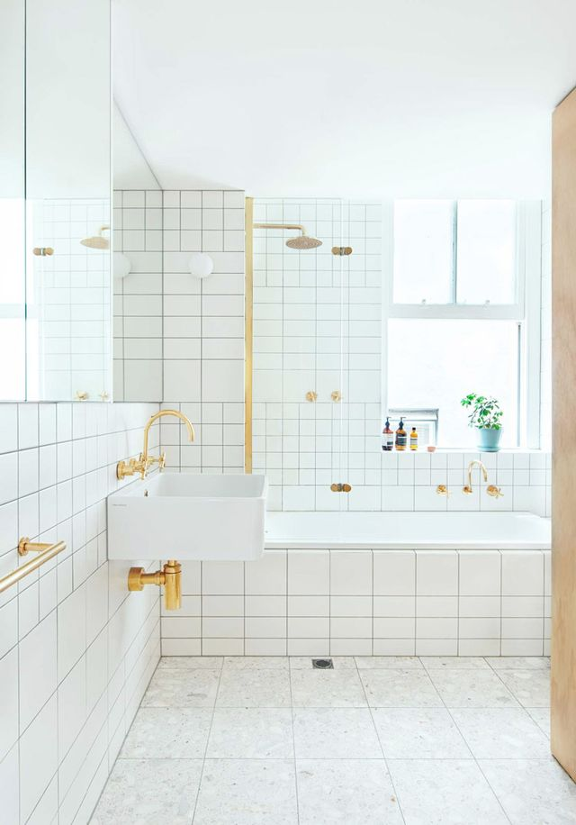 The variety of tile sizes addinterest to this white bathroom, beautifully accented with gold hardware and plumbing.
