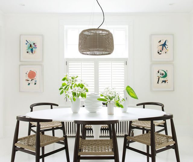 All you need to break up the white here is some wooden chairs and a textured pendant lamp. We love the artwork in neutral and subtle colors, the perfect accent against the milky wall.