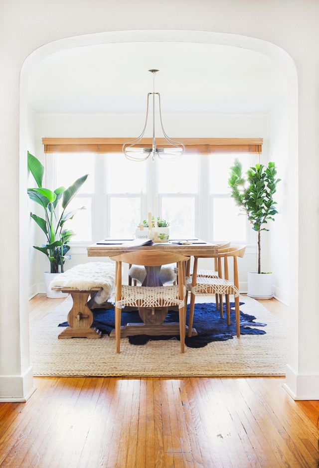 """This stark white space was given a """"half bungalow half fluffy minimalist"""" vibe with wooden dining chairs and that amazing modern chandelier. The weaving and the rugs bring texture and color."""