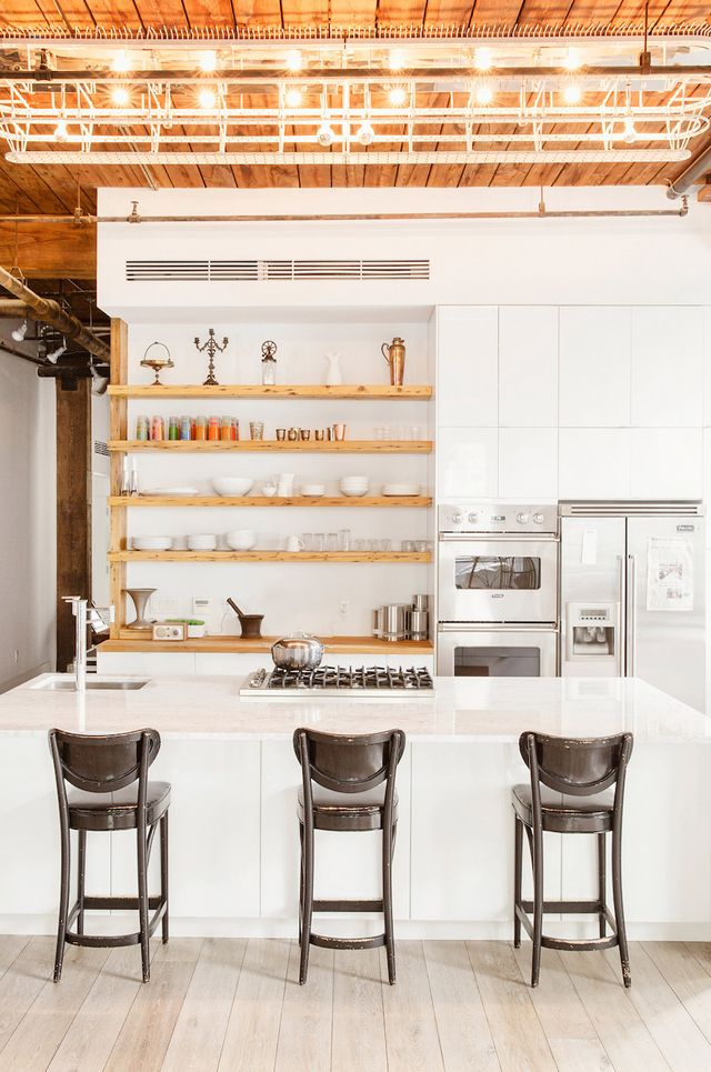 Knotty wooden shelves for displaying glassware and servewareserve as a focal point in this creative living space and workspace in Williamsburg, Brooklyn.