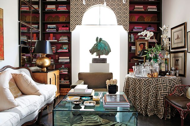 Give your living room a smart update with curated shelves stacked with collectibles and covetable reading material. Add pops of color against a bright background hue.