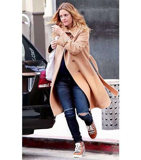 This long, belted style by Max Mara elevates ripped skinny jeans and sneakers so the look is appropriate for a casual, early dinner. 
