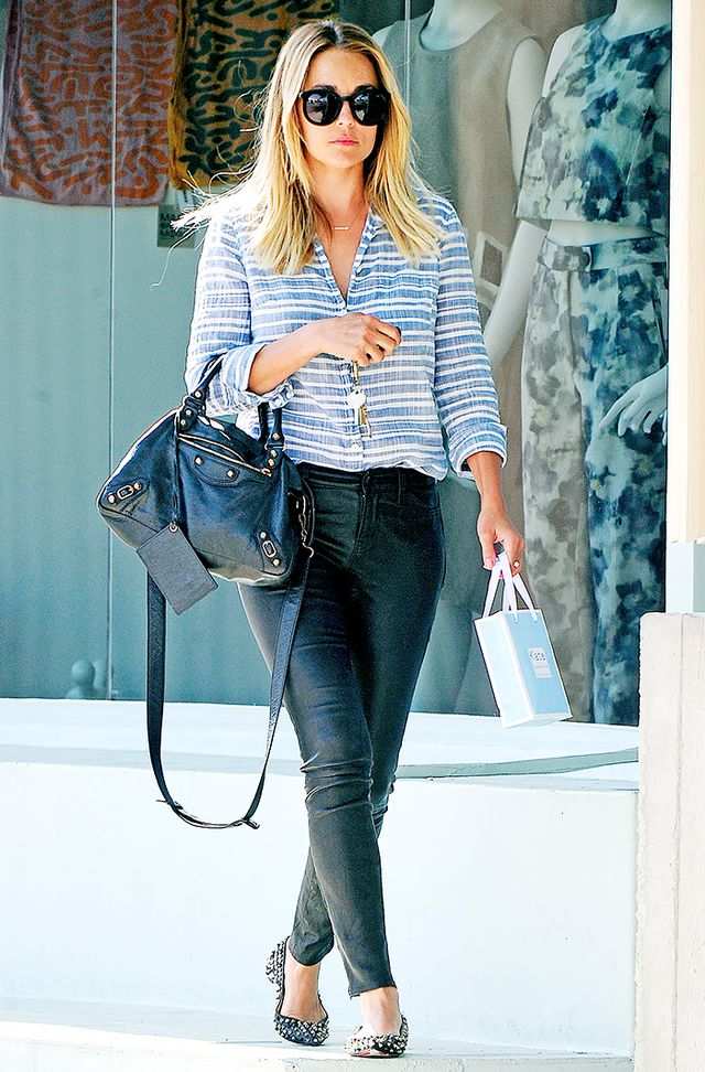 A menswear-inspired button-down shirt, tucked into black skinny jeans and paired with edgy accessories, is a no-fail Casual Friday look.