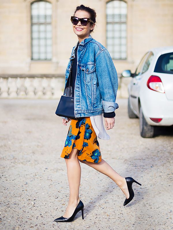 A vibrant floral skirt and sophisticated pumps are the perfect companions to an oversized denim jacket.